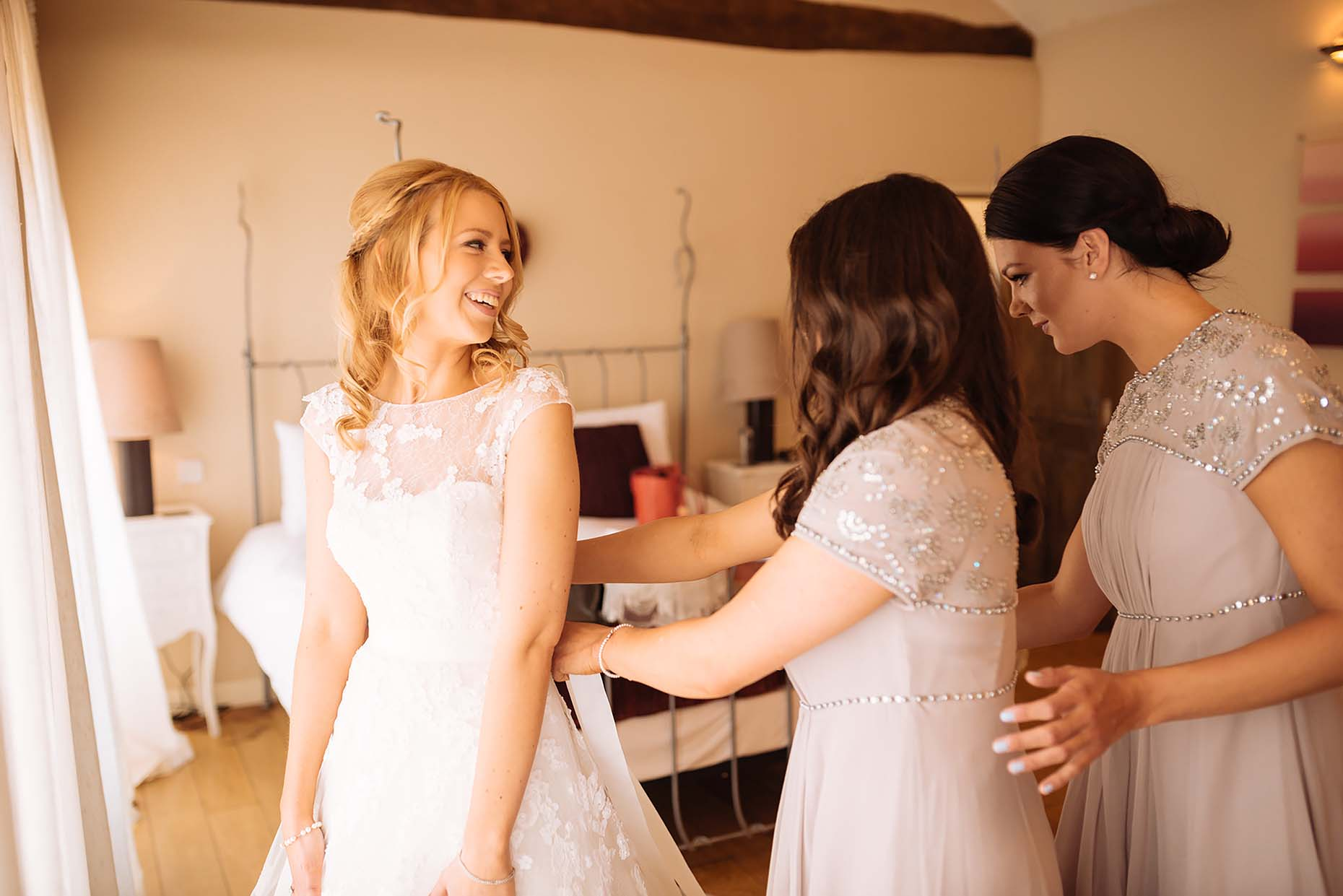 bride-with-bridesmaids-putting-on-dress-northampton-wedding-photographer-emma-dodmoor-12