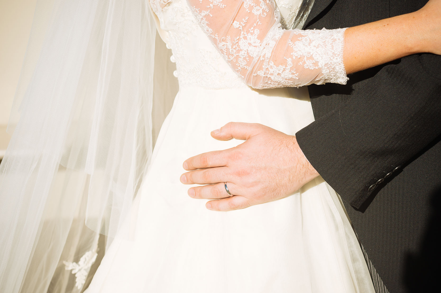 wedding-ring-groom-hand-on-dress-belgrave-square-garden-london-15