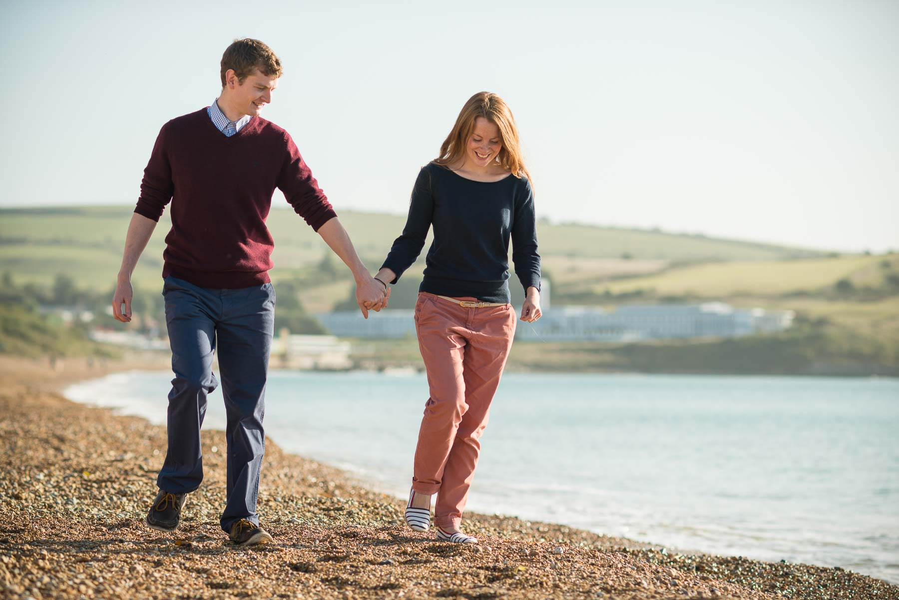 weymouth-beach-zoe-engagement-shoot-happy-couple-walking-10